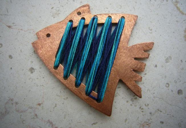 Pendente a forma di pesce realizzato a traforo su rame e innesti di fili colorati