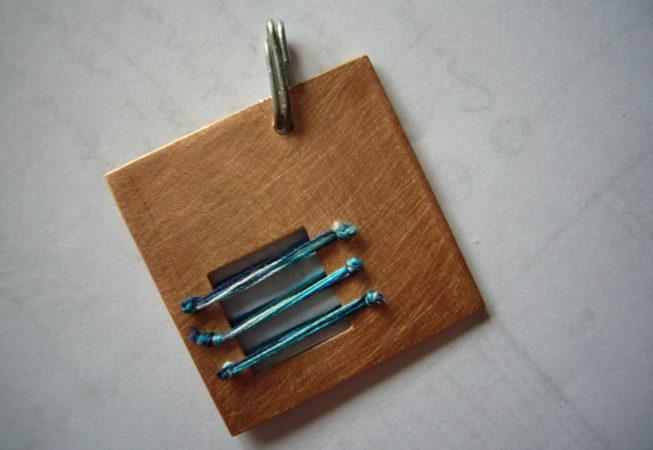 Pendente realizzato a traforo su rame e innesti di fili colorati