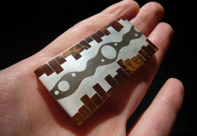 Spilla: tarsia realizzata con differenti metalli: rame, argento e shibuichi